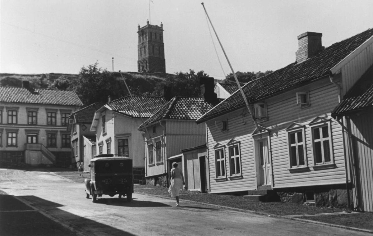 Gateliv i Tønsberg. En kvinne går og en bil kjører opp en gate blant trehusene. I bakgrunnen sees Slottfjelltårnet.