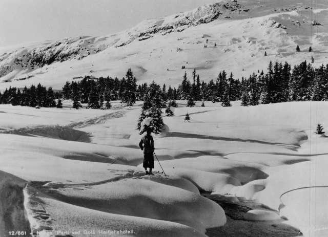 Avfotografert postkort. En enslig skiløper står ved en åpen bekk i et snødekt vinterlandskap i nærheten av Gålå høyfjellshotell.