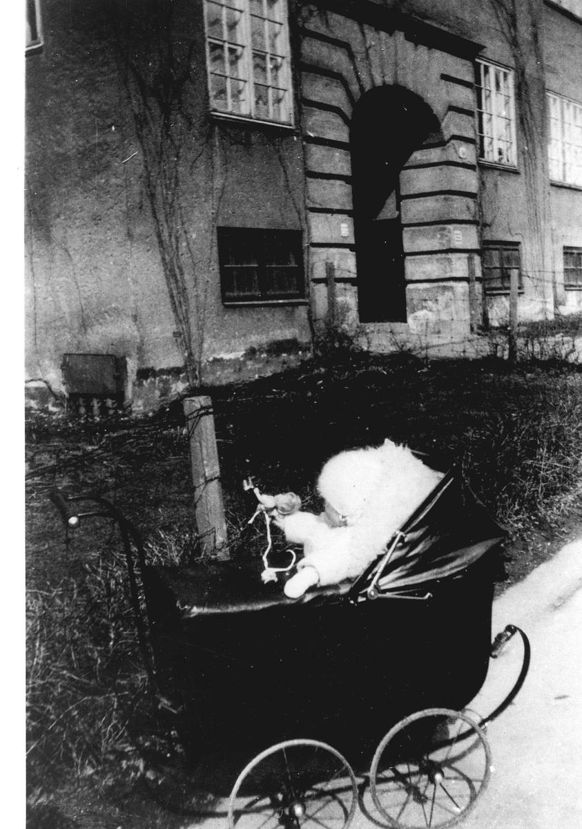 Barn i barnevogn foran bygård. Familiens datter Jorunn Fossberg i barnevogn foran sitt barndomshjem i Jacob Aalls gate 60, Oslo i 1928. Fra Jorunn Fossbergs familiealbum.