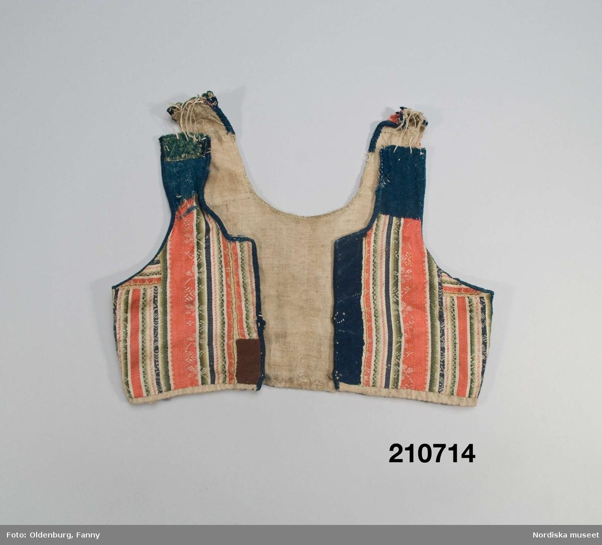 """Livstycke """"bod"""" som varit fastsytt på en kjol. Av varprandig yllesatin i rött, blått, vitt och gröna nyanser med invävda vita mönsterbårder, kvaliteten kallas blommerad kalmink och vävdes av kamgarn och glättades. 2 framstycken  och ett bakstycke med 3 påsydda lila band i ryggen. Livstycket består av flera hopskarvade bitar, dels av kalminktyget dels av mörkblått kläde samt blått och grönt vadmal (på axlarna och vid ena framkanten där det även finns en brun bit).I sidorna iskarvad med på ena sidan gult kläde på den andra mörkblått kläde. Kantad kring ärmhål och hals/framkant med blå vadmal och blått kläde. På insidan av framkanterna svart kläde, knäppning med  2 par hakar och hyskor av mässing. Fodrat med oblekt ojämnt vävt linnelärft Anm. Slitet, avklippt på axlarna där livet förlängts med öglor av dubbelt lingarn. Sådana blommerade kalminker vävdes främst i England och kom till Norden under 1700-talets andra del och blev moderna i folkligt dräktskick.  /Berit Eldvik 2007-09-20"""