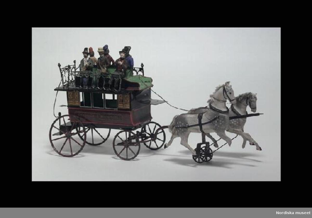 """Inventering Sesam 1996-1999: L 34   H 17  (cm) Ekipage, omnibus, leksak, vagn av lackerad plåt i vinrött, gult och svart, tre fönsteröppningar på varje långsida, baktill öppningsbar dörr, innuti två bänkar, framtill säte för kusk, taket med grönlackerade bänkar för 6 passagerare och räcken av grönmålat tenn. 6 st passagerare av massa föreställande män i olika nationella kläder. Långsidorna med text """"MALZEVILLE A BONSECOURS"""". Hjul med ekrar av metall, lackerade i vinrött, främre hjulparet vridbart, tistelstång. Två hästar av skuret trä, målade, apelkastade, förbundna med stag till litet hjul. Hjuldriven travfunktion; hästarna rör sig upp och ned vid gång. Anm: Kusk och 4 st passagerare i vagnen saknades redan vid förvärvstillfället.  Birgitta Martinius april 1998"""