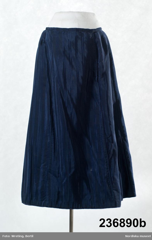 2-delad klänning av mörkblått randvävt halvsiden. a-b samt löst skärp c.  a. Liv figursytt på foderstomme av  ljusgul bomullskypert i fiskbensmönster. 2 framstycken och ett ryggstycke med ett rundat skört bak som dock stoppas ned i kjolen, Fram djupt V-ringad med  2 breda lagda veck som  löper i V-form från axel ned mot underkanten både fram och bak. Längs med vecken även en 3 cm bred  svart maskingjord spets . I ringningen isättning av samma tyg med en mängd tvärgående stråveck, tättslutande ståndkrage  styvad med något mellanlägg. Isydd lång ärm, svängd med 2 sömmar, något rynkad på ärmkullen, snäv vid handleden. Mitt bak i midjan en fastsydd häkta att fästa mot kjolen.  b. Kjol av 7 sneddade våder, sydd på foderstomme av svart bomullslärft s.k domestik. Framvåden markerad med nedsydda veck vid sömmarna. Kjolen slät framtill och rynkad bak i midjan mot en 2 cm bred linning av samma tyg. Mitt bak i linningen en fastsydd hyska att häkta mot livet. Dolt sprund i vänster framsöm knäppt med  5 tryckknapapr och överst en hake och hyska. Infälld ficka i sprundet. Skoning i nederkanten av samma tyg som fodret. I kanten slitband med plyschkant. Anm. 10-12 cm av tyget invikt upptill vid linningen. Kanske ett sätt att inte klippa bort tyg om man skulle vilja återanvända det senare. Det var mycket vanligt att just tygrika kjolar kunde sys om till annat. c. Löst skärp av samma tyg.  Veckat på längden. Ofodrat, söm mitt bak, 3 fastsydda stålfjädrar på insidan. Knäpps med 3 svarta hakar och tränsade trådöglor  Klänningen bör vara sydd efter 1903 då Prym uppfann tryckknappen. /Berit Eldvik 2011-09-08