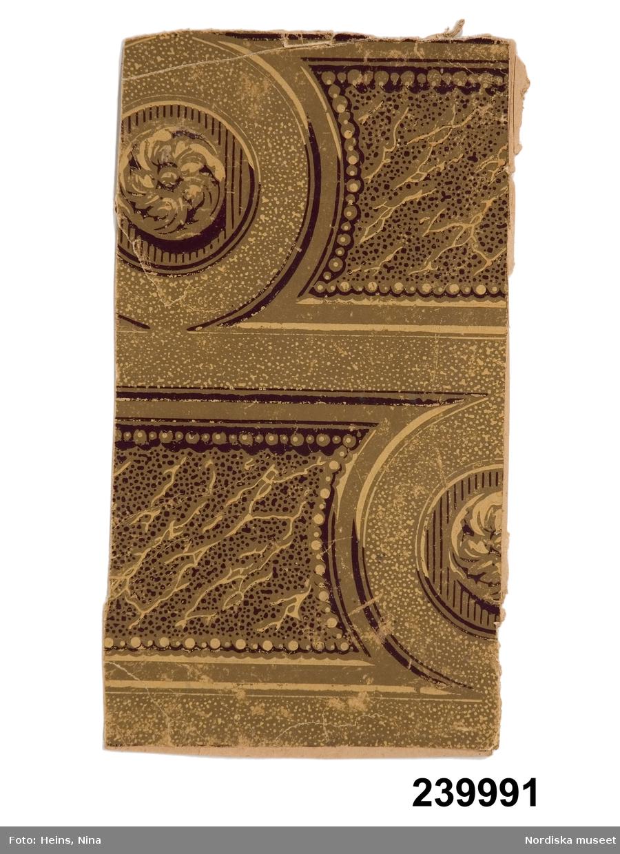 """Huvudliggaren: """"Tapetprov, av papper, med tryckt dekor med mönster av stenimiterande karaktär. Enligt påskrift: från 1870-talet. Jfr E.U. 40.414.""""  Katalogkort: """"Tapetprov, 33 x 18,5 cm, klistrad på papp...""""  Stenimitation i bruna toner.  Anm: Veck, smärre färgslitage. /Cecilia Wallquist 2007-08-23."""