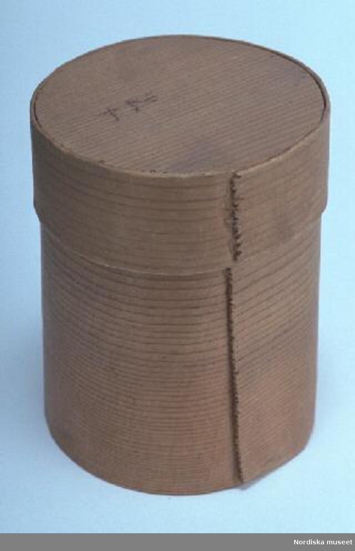 Inventering Sesam 1997-1998: Diameter 7, H 9 cm Ask (a) med lock (b), cylinderformad. Botten, lock och svep av barrträ, antagligen furu, utan falsar. Svepen fästade med lim. Hopfästning av svepen med lim. Ett par tecken på lockets ovansida, skrivna med bläck. Bottensvepet litet trasigt i överkanten med bitar borta. Agnetha Blomberg 1997