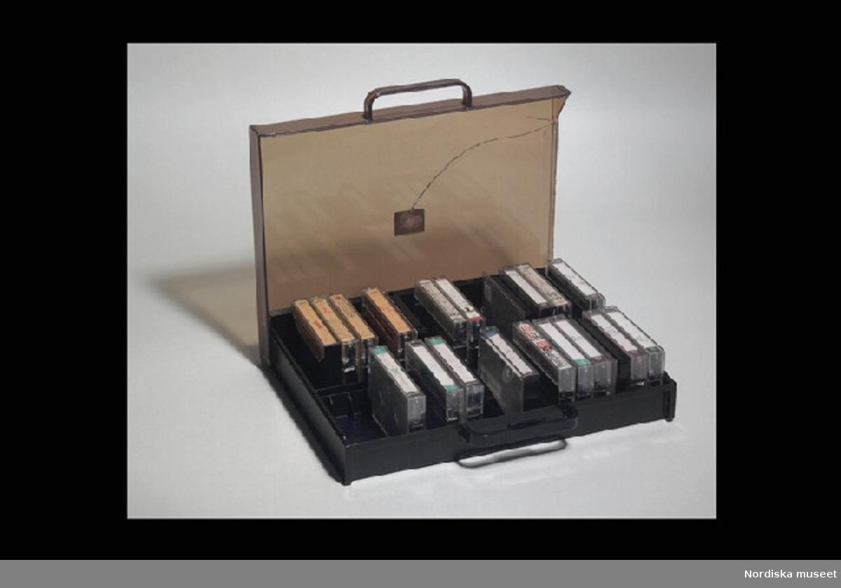 """Inventering Sesam 1996-1999: Kassettväska L 33 cm, B 25,5 cm, H 6 cm Kassettband L 10 cm Kassettbandsfodral L 11 cm Kassettväska med kassettband. Väska/lådan av brun hårdplast, transparent lock. Handtag. Under väskan etikett med text """"Made in Hong Kong"""", på locket etikett """"KASSETTVÄSKA"""". Locket har en spricka och gångjärnsfunktionen är trasig. väskan fack f¿r kassettband. I väskan finns 20 st kassettband, 18 st kassettbandsfodral av transparent plast (två med endast locket kvar) med omslag av papper, ett omslag ligger l¿st) På omslagen står det skrivet vilka dataspel som är inspelade på banden. Dataspelen är hemmakopierade på vanliga kassettband av märket Sony, Maxell (Japan), Philips (Beligien), AGFA (Tyskland)  och Basf (Tyskland). Vid spel kopplades tangentbordet till en vanlig TV, en bandspelare, i vilken kassettbandet stoppades, och en transformator, ev även till joy stick. Har brukats av Axel Brundin (f¿dd 1977) tillsammans med nedanstående f¿remål. Dataspel och tillh¿rande f¿remål; Tangentbord ivn.nr 321.617 kasettbandspelare inv.nr 321.618, transformator inv.nr 321.619, Kasettväska med kassettband med olika dataspel inv.nr 321.620:1-24, tre joy sticks inv.nr 321.621 och 321.622, skokartong inv.nr 321.623 (i vilken kassettband f¿rvarades)  och Kassettband med spel 321.624-321.639 Instruktionsb¿cker, band- och kundf¿rteckning finns på arkivet. Bilaga EB 1995 [Elisabet Brundin] Leif Wallin 1998"""