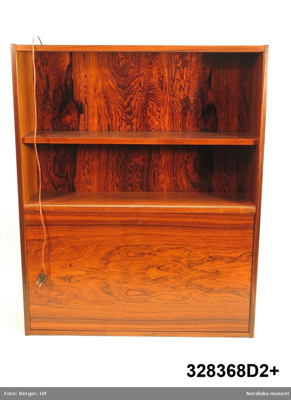 """a-e: Bokhylla, """"Excellent"""",  med TV-bänk samt bar- och vitrinskåp, jakarandafaner på spånskiva, IKEA, 1968.   Hyllan består av fyra sektioner med hyllor löst placerade på underredet. Skåp- och byråunderdelar med ryggar av masonit, fastnitade. Kvadratiska ben, fastskruvade i underredet. Lådsidor m.m. av björk och lådbottnar av vitlackerad masonit. Flyttbara hyllplan. Draghandtag och gångjärn av mässing.  Enligt IKEA-katalogen 1968 är ytan plastbehandlad.  Hyllan uppställd, från vänster till höger: a:1+) Skåp med två dörrar samt a:2+) hyllöverdel, ett fast och två flyttbara hyllplan. Överst vitrindel med två skjutdörrar av glas (höjd 53,5 cm, bredd 41,5 cm). b:1+) Byrå med tre lådor samt b:2+) hyllöverdel med tre flyttbara hyllplan.  c:1+) Tv-bänk med en låda samt c:2+) hyllöverdel med tre flyttbara hyllplan. d:1+) Skåp med två dörrar samt d:2+) hyllöverdel med 1 flyttbart hyllplan. Överst vitrindel med två skjutdörrar av glas (höjd 53,5 cm, bredd 41,5 cm), därunder ett barskåp med spegel som bakvägg, utrymme för flaskor till vänster och två glashyllor (48 x 19,5 cm) till höger. Barskåpet med fällbar klaff med lås. Belysning monterad i skåpets överkant. e) Nyckel till barskåpets klaff. L 4,3 cm.  Möbeln har använts av givarinnan, Berith Helldén, f. 1945, hemmafru, och hennes man, Lars-Göran Helldén, f. 1946, inköpare, Tungelsta. Paret gifte sig 1967 och bodde som nygifta i en liten lägenhet i Borås. När de fick möjlighet att flytta till en större lägenhet i samma stad, utökades vardagsrumsmöblemanget. Hyllan inköptes 1968 på IKEA i Älmhult. Enligt IKEA-katalogen 1968 kostade de fyra hyllsektionerna totalt 2484 kronor. Hyllan har använts som förvaringsmöbel i vardagsrummet i Borås och i familjens nuvarande bostad i Tungelsta fram till våren 2005, då den inköptes av museet.  Hyllans innehåll har dokumenterats och en utförlig intervju med Berith Helldén har gjorts 2005-05-09 (se arkivreferens). /Anna Womack 2005-10-18"""