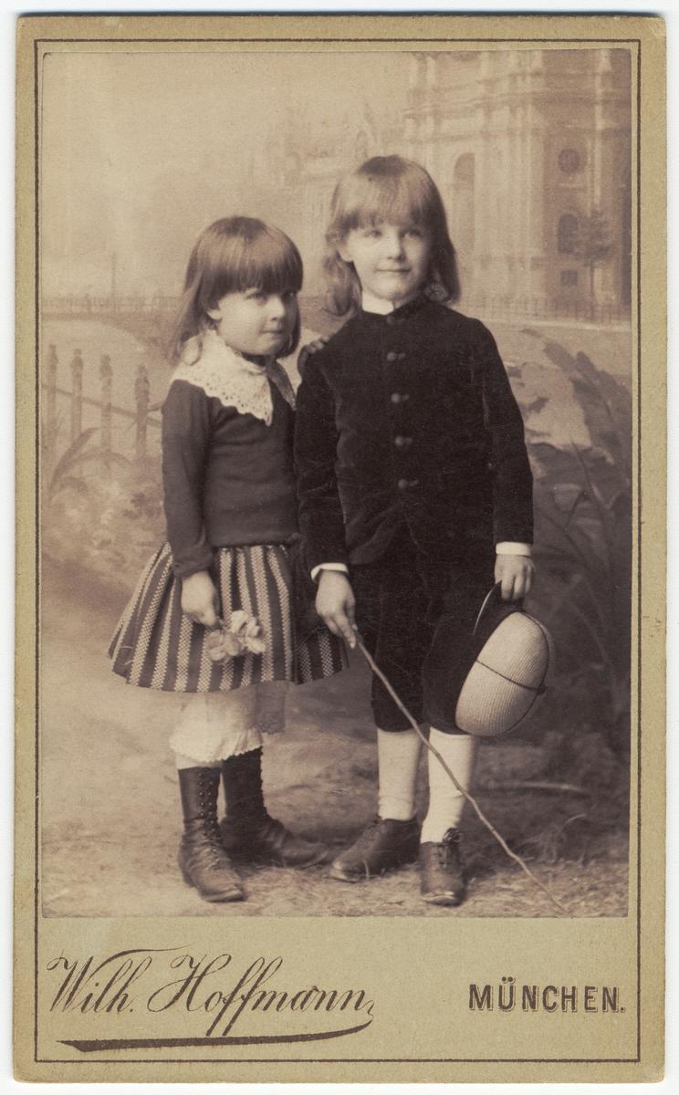 Ateljéporträtt av två barn, en pojke och en flicka. På baksidan påskrift med blyerts april 1888.