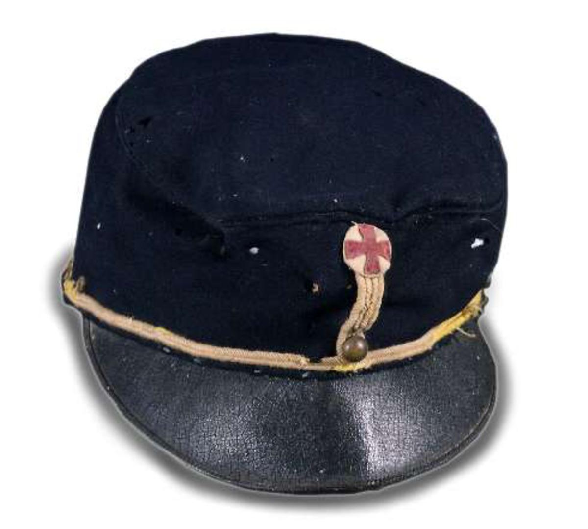 """Uniformsmössa av mörkblått kläde. """"Modell 1895"""". För kavalleri. Liten svart skärm. Gula snoddar. Tre runda ärgade knappar. Mitt fram sitter kompanimärket, rund tygrundel med rött kors."""
