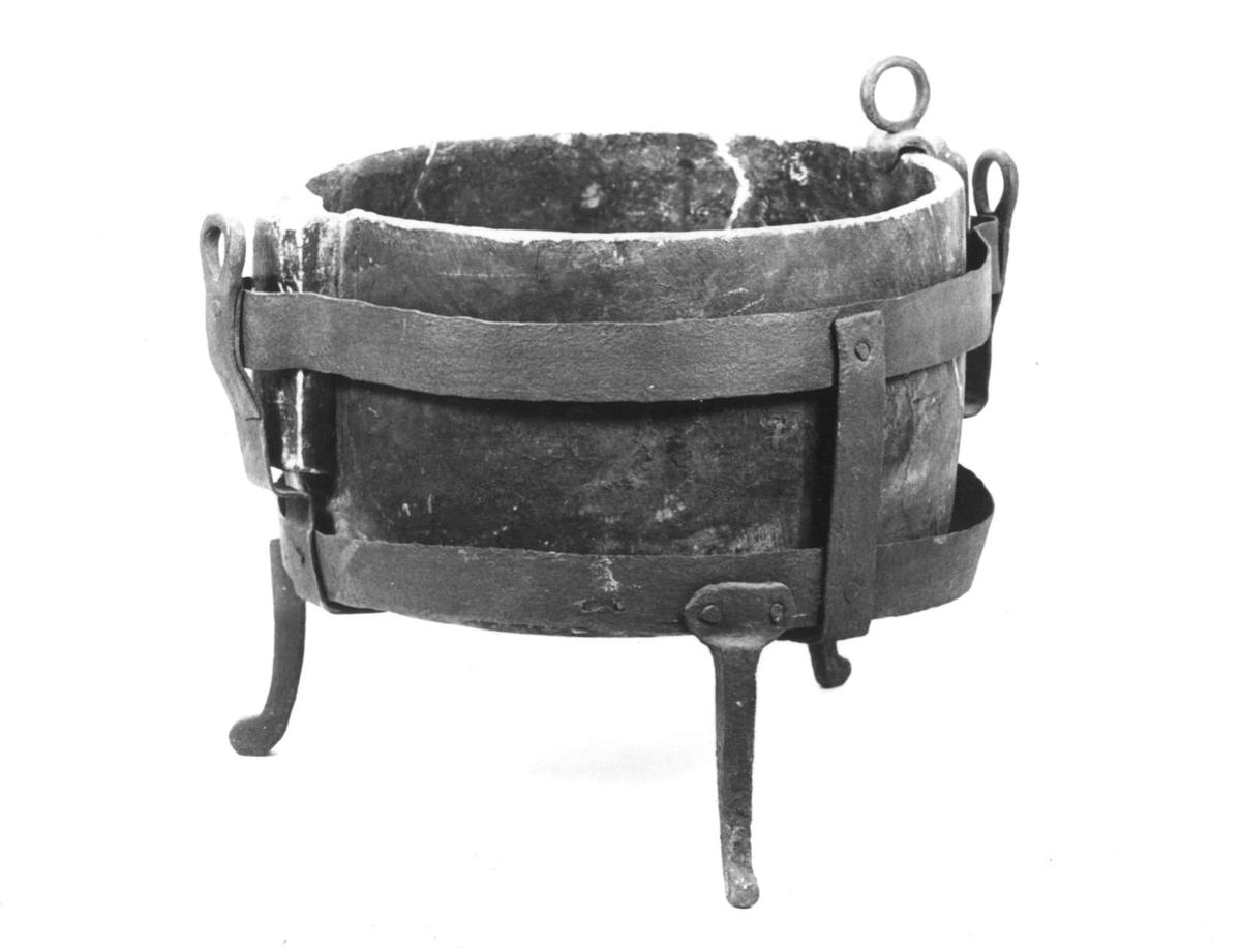 Grytställ av järn, runt, tre fötter, två handtag, två vågräta band samt i botten två korslagda band.