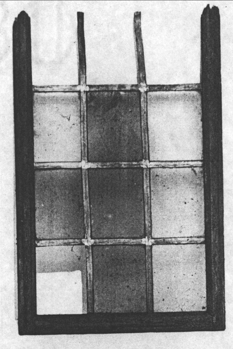 Fönster med träram, blyspröjsar och 12 rutor av glas i varierande  färg. Beslag av järn.