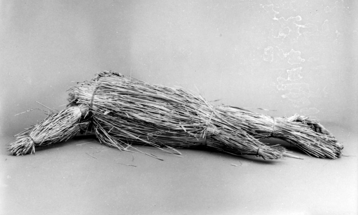 Julbock, enkelt bunden av halm, två flätade horn, framåtriktade framben, flätad svans.