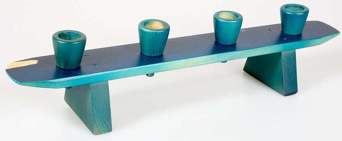 Ljusstake av trä för fyra ljus. Ljusstaken är målad i en blå färg som träådringen lyser igenom. En träflisa har lossnat i ljusstakens ena kortsida.