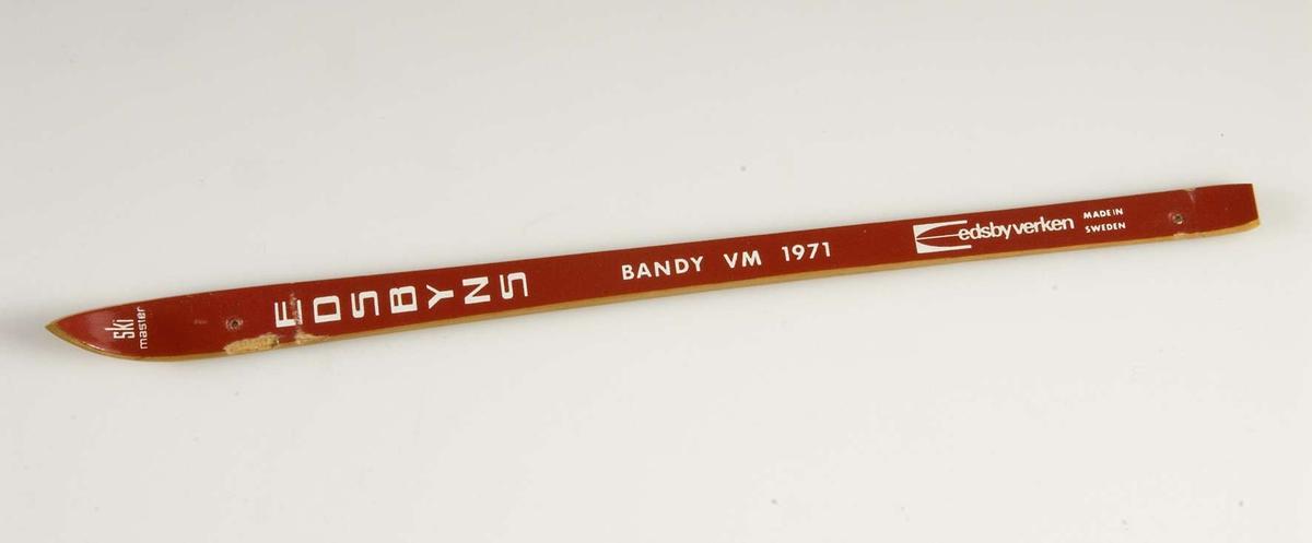 Liten skida av trä, rödmålad. Från bandy-VM 1971. På skidan texten: Skimaster. Edsbyns. Bandy VM 1971. Edsbyverken. Made in Sweden. Två hål för upphängning.