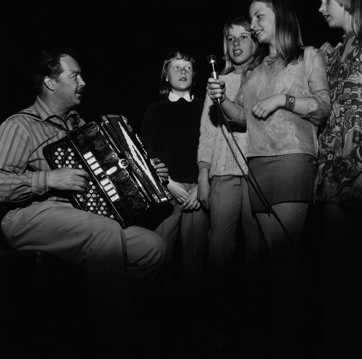 Musikern Egron Hultgren och uppträdande flickor på Unga Örnars avslutningsfest i Sveasalen