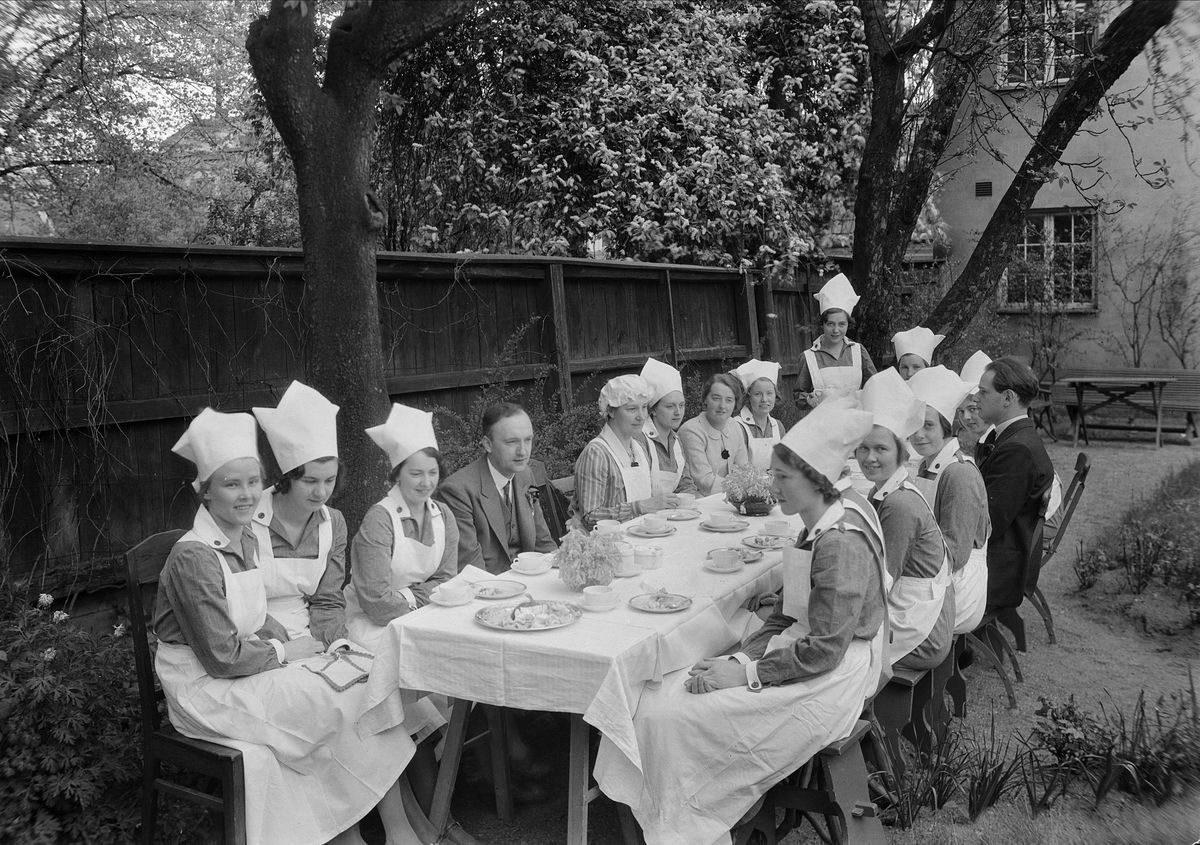 Nils Ålenius med flera personer vid långbord i trädgården - Fackskolan för huslig ekonomi, Uppsala