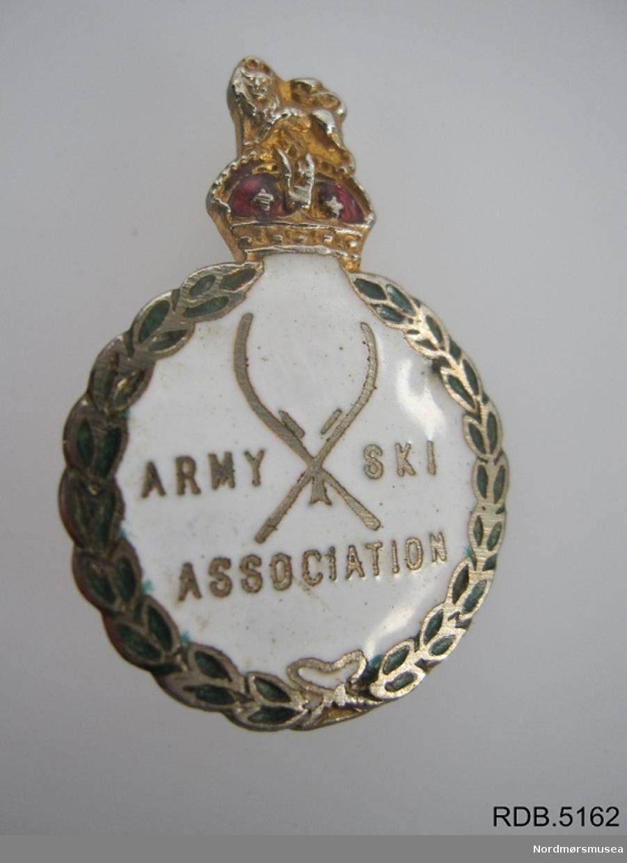 Rund pins med ei kongekrone på toppen. Ei nål på baksiden. Army Ski Associations logo på forsiden.