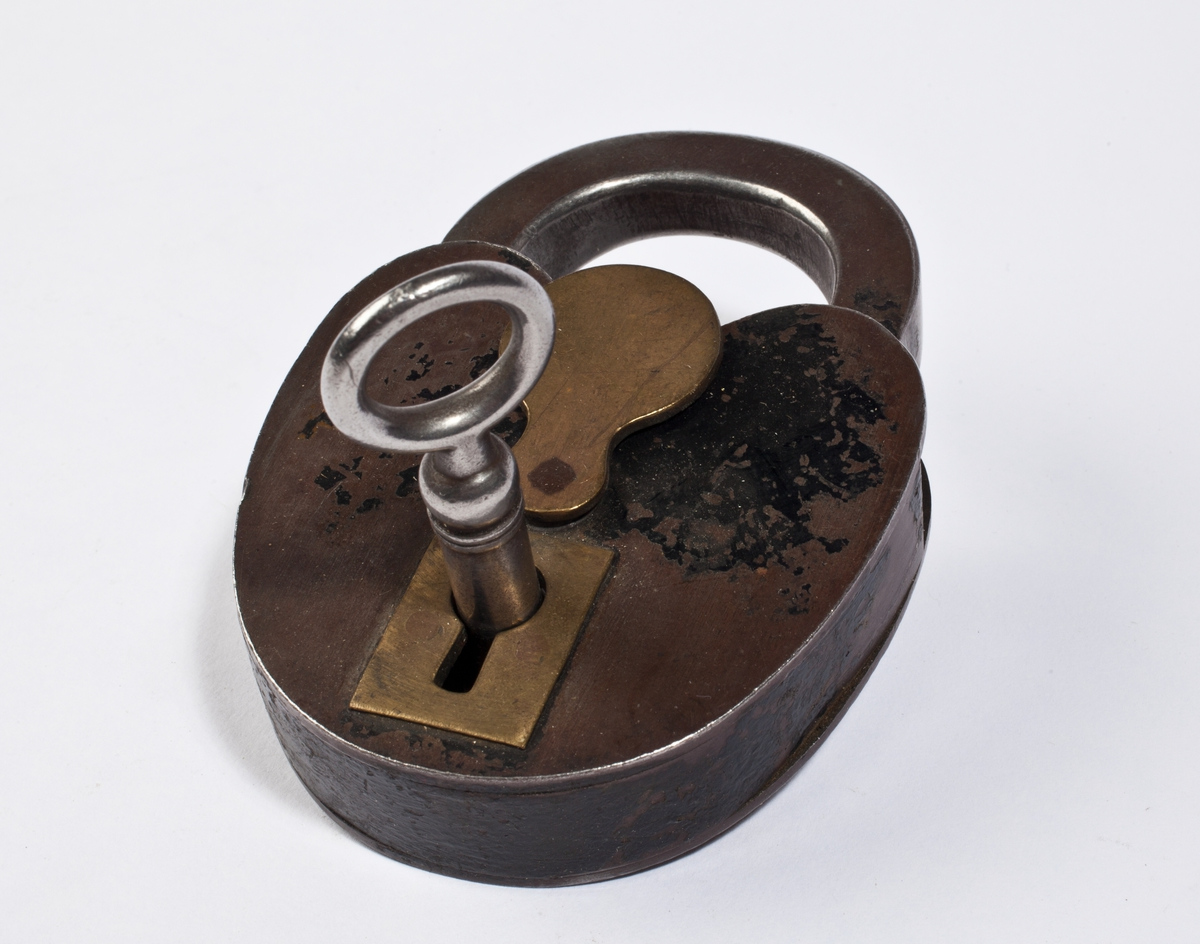 Hengelås med ovalt låsehus som er innsvingt øverst under bøylen. Den har tilhørende nøkkel og klaff til å dekke nøkkelhullet.