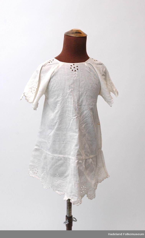 Kjole og lue til jentebarn (1-2 år). Kjole og tilhørende kappehue i hvitt bomullstoff (cambric) med engelsk (hull)broderi. Tidlig 1900.