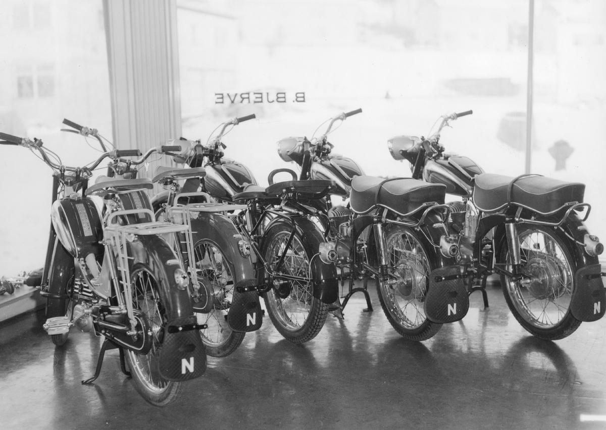 Forhandlers butikk: motorsykler og mopeder i et butikkvindu