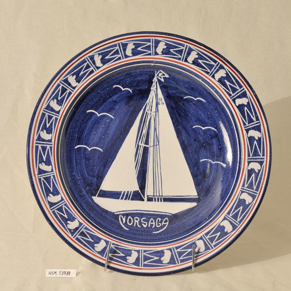 Keramikkfat med tegning av seilbåten Norsaga som har tilhørt Charles Ulrik Bay. Blått fat med hvit dekor.