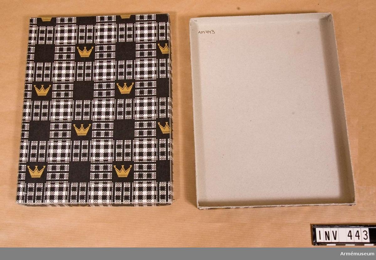 """Förvaringsask till minnestecken """"Ehrengabe"""". Pappersask med lock och botten. Askens pappersomslag har bilder av hertigkronor i guldfärg. Samhörande nr är 294-299, 321-350, 400-448 (442-443)."""