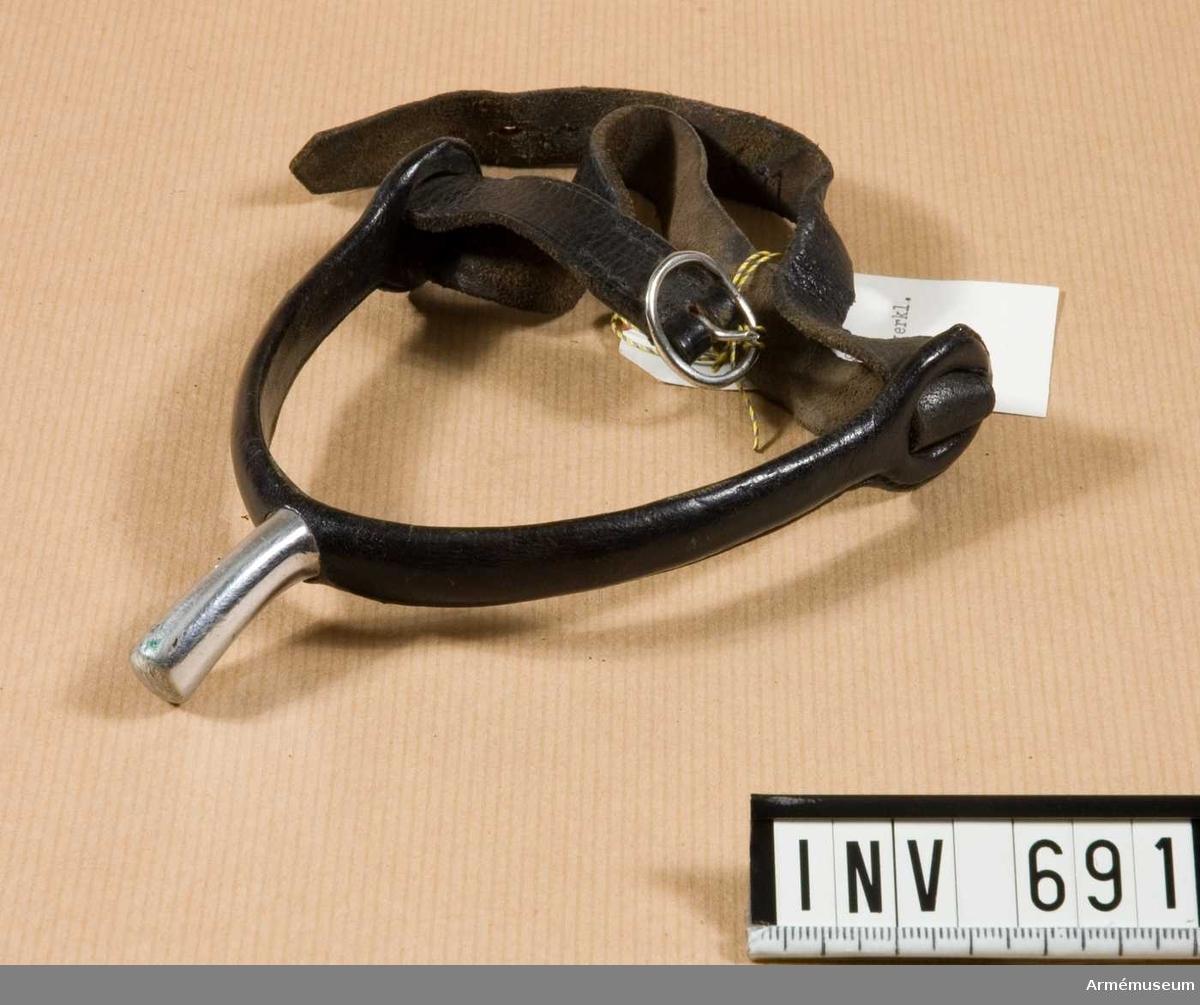 Av rostfritt stål, utan trissa. Överklädd med svart läder och således avsedd för vinterbruk (lädermaterialet hindrar stålet från att leda kylan). En enkel 10 mm bred svart läderrem håller sporren på plats.