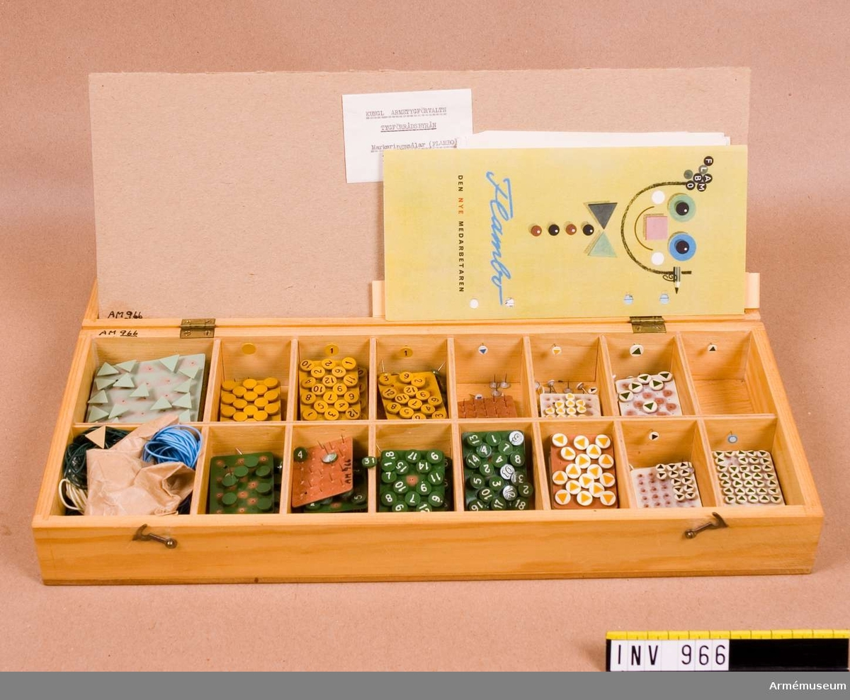 Innehåller markeringsnålar, avsedda för markering på kartor. Lådan är tillverkad av fernissat trä med beslag av mässing.