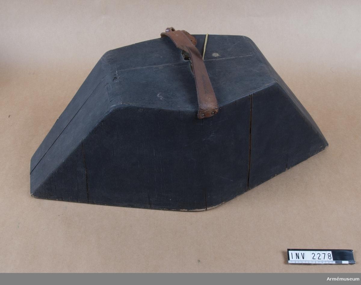 """Av svartmålat trä och har form efter hatten. Uppfläkes på  längden i mitten och för detta finns två gångjärn i botten. Lådan knäppes med låsbar hasp märkt """"Aug. Stenman, Eskilstuna"""".  Asken bärs i en läderrem som knäppes med läderknapp. Denna har lossnat och förvaras tills vidare i asken. I knäpphålet sitter en adresslapp i läderfodral. Skrivet med skrivstil """"O.G. Thörnell, Östermalmsgatan 72, Stockholm"""".  Fodralet är klätt med lila bomullsfoder som är klistrat vid träet. Någon vaddfyllning emellan. Inuti asken sitter ett visitkort fast med häftstift. Text """"Generalmajor O.G. Thörnell, inspektör för infanteriet, Nybrogatan 76, Stockholm, tel 61 26 10""""."""