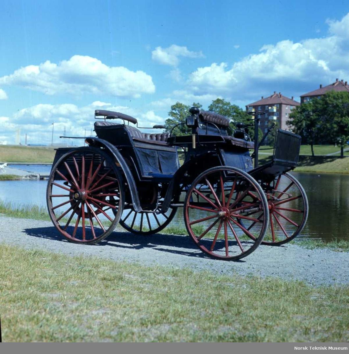 """Utstillingstekst basert på Lindtveit:  I 1895, snaut ti år etter at den første brukbare bil med forbrenningsmotor var laget, var det noen som fant ut at en slik kanskje nettopp ville være noe for vårt land med de lange avstandene.  Jernbanenettet var på denne tiden ganske godt utbygd, men det var likevel mange steder der det neppe noen gang ville komme noen jernbane. Og jernbanen oppover vårt viktigste dalføre, Gudbrandsdalen var ikke kommet lenger enn til Tretten. Det ville derfor passe fint å fortsette med automobil derfra og til Åndalsnes (Veblungsnes). Herrene som satte i gang dette modige foretakende var Brukseier Østbye ved Gjøvik Støberi og mekaniske Værksted, handelsreisende H. Mølmen, fabrikkeier H.C.Hansen og ingeniør S.R.Svendsen. Det var de to sistnevnte herrer som fikk i oppdrag å dra nedover i Europa for å finne en passende motorvogn. Den 14. november 1895 meddelte avisen """"Social-Demokraten"""" sine lesere at """"petroleumsvogner"""" var ført inn i landet. Den 4.  januar 1896 var vognen på plass på Gjøvik. Avisen """"Samhold"""" meldte at vognen fortsatt stod i en kasse, men at nysgjerrige hadde slått et hull i kassen for å ta en kikk på """"raringen"""". Det ble på våren i 1896 foretatt en del prøveturer omkring Gjøvik, og det ser ut til at det har vært visse vanskeligheter. Den 16. mai 1896 uttaler i nemlig eierne at det fremdeles var en del ting å rette på før vognen kunne settes i fast drift. I løpet av sommeren 1896 ble vognen om sider satt i drift på noen prøveruter i Gudbrandsdalen. Det sies at den kom i fast rute mellom Tretten og Ringebu. Det ble imidlertid ikke noen suksess. Det fortelles at det stadig vekk var kluss med motoren. Det kom vel delvis av at det ikke var noen som visste hvordan den skulle passes. (Erfaringer fra prøvekjøring ved Norsk Teknisk Museum har også vist at motoren er vanskelig å drive og vedlikeholde.) Bilen ble kjørt av Halvdan Nilsen fra Gjøvik. Folks begeistring kjølnet nok etter hvert. Bilen skremte hestene, og den måtte stadig stoppe p"""