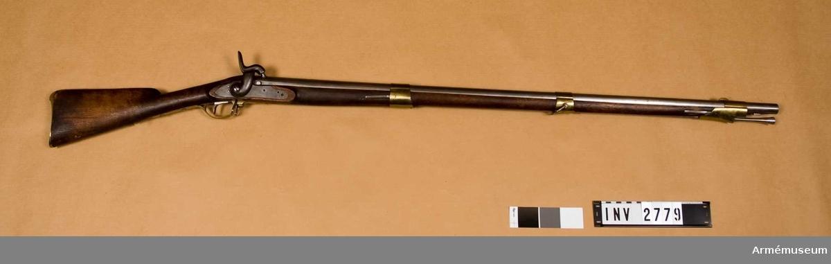 År 1849 antogs förändringsmodeller till slaglås från flintlåsgevär m/1815. Stockar, beslag, laddstockar och bajonetter äro oförändrade. På geväret är knallhattstappen inskruvade i själva pipan. Det gamla fänghålet är tärnat och en utskjutande cylindrisk järntapp angiver det ställe där det suttit. Låset saknar varhake men har fått ny nöt med lågt halvspänn.   Pipan är tillv. hos Carl Gustav stads. Låset märkt H 1446 (Husqvarna). tnr 1446, 1823.  Samhörande nr är 2779-2780.