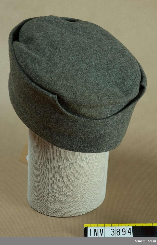 """Förslag till mössöverdrag fm/1940. Enär stora delar av de inkallade år 1940 var utrustade uniform  m/1923 och äldre modeller, väcktes frågan om en varmare  huvudbonad i form av ett överdrag till befintliga mössor. Två  modeller konstruerades; denna av gråbrungrå kommiss och en av  vitt ylletyg (fotlappsväv). Några försök kom aldrig till stånd  då utrustningen med uniform m/1939 blev allt vanligare och i  samband med det blev modellen ej aktuell.I kullen märkning som anger storlek 60 f stl 55/56 samt """"I 11""""."""