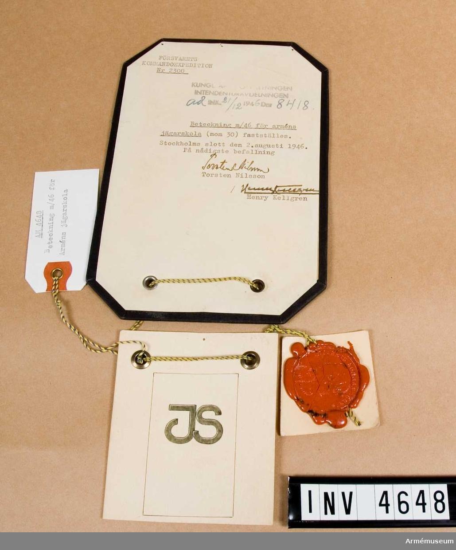 """Tillverkas av bronsfärgad metall. Utgöres av bokstäverna """"JS"""". Anlades av skolans personal på axelklaffar till vapenrock/kappa m/1939. Till uniform m/1952 i mattförgyllt utförande. För uniform m/1960 utformade ädelsmed Sigurd Persson ett nytt förbandstecken i form av varghuvud under kunglig krona, förgyllt."""