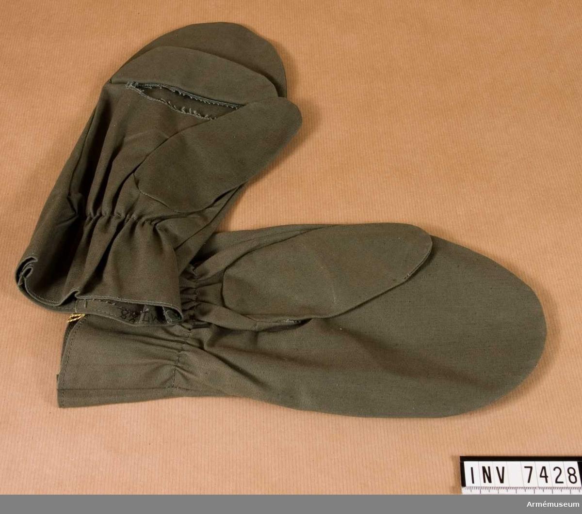 Vindtyg. Av grönt vindtyg. Höger handske har öppning för fingrarna och är försedd med ett lock för tillslutning av öppningen. KAFI dnr 3900/53.