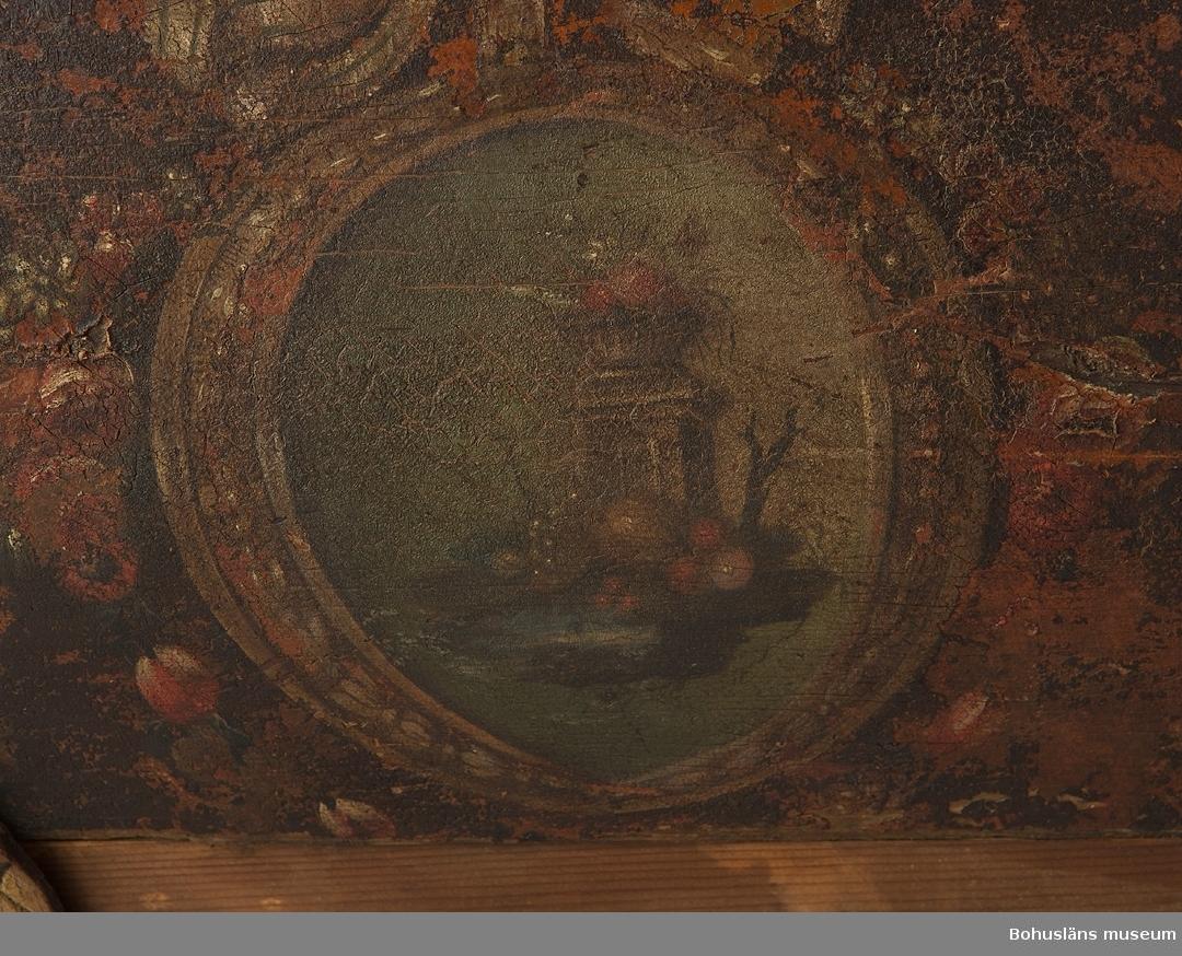"""Rikt utskuren slädkorg i (norskinspirerad) rokoko på svängda medar som går ihop framtill. Målad med brunt, engelskt rött och guld. Runt en av medarna är en ring av ihopsytt läder med rep inuti. Längst upp är en duva utskuren samt målad med guldfärg. Sidostycken med målade pannåer föreställande medaljonger med blomkvist samt rosett upptill i grönt, rött, vitt mot brun bakgrund. Målad inuti med engelskt rött. Järnet har bladslingor gjutna i relief. Vissa delar är sekundära.  Se Knut Adrian Andersons """"Katalog I, A. yngre föremål"""" under Uddevalla museum/förening D 2A:1.  Ur handskrivna katalogen 1957-1958: Släde (förmodl. felident. tidigare) L. 2m. Snidad i rokokostil m. målade medaljonger; huvudsakl. rödmålad; längst fram en duva, skuren i ek. Järnbeslag rostiga, smärre defekter, skrangliga."""