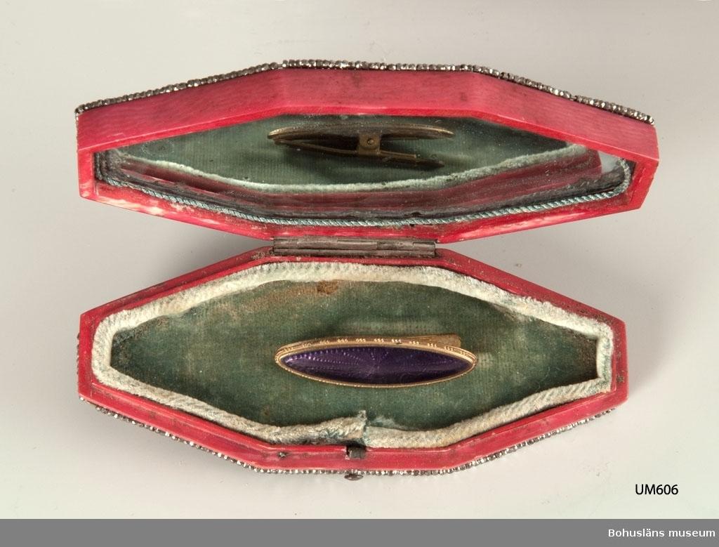 Ur handskrivna katalogen 1957-1958: Litet etui m. kanter av stålpärlor. L. 10 Br. 4. 8 -sidigt rött etui. På locket 3 medaljonger. inuti locket spegel. Föremålet helt.  Lappkatalog: 60  Etui för förvaring av av smycke från 1800-talet. Trolig datering: 1830 - 1850-talet. Clipset som ligger i etuiet hör inte föremålet.