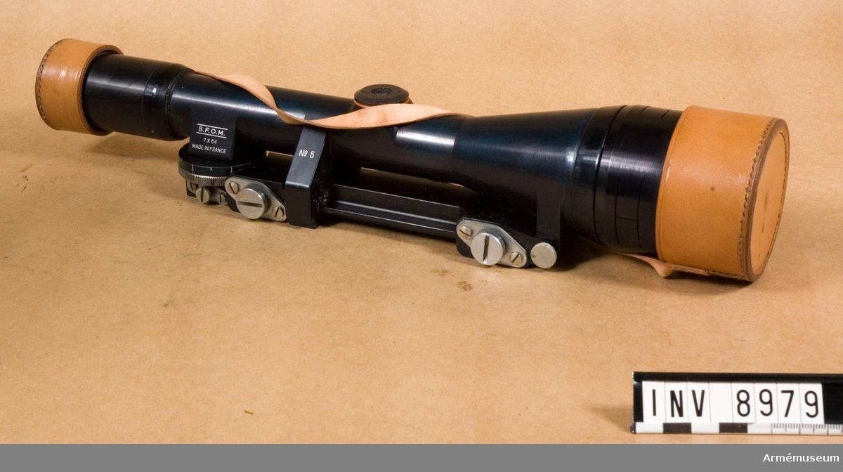 Med hållare. Märkt S.F.O.M. 7x64 Made in France. Bestående av: 1 st kikarsikte med hållare, 1 st linsskydd av läder.   Tillverkningsnr 5  Samhörande nr är AM.8979 - 8980