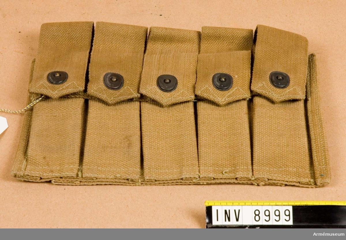 Magasinväska till kulsprutepistol m/1940, Thompson.För 5 st 20-skotts stångmagasin till kulsprutepistol m/1940.5 st stångmagasinfickor med tryckknappslåsning. Tillverkad i ljusbrunaktig väv.