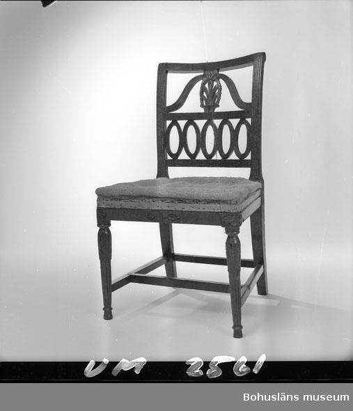 """Denna stol är identisk med UM002560. Stol i gustavianskt utförande. Tillverkad i Lindome. Redan vid tillverkning sattes klossar in under sargen; dessa är pluggade. Alltså originalklossar i detta fall (uppgift från Birgitta Maritinus, Mölndals stadsmuseum i september 2008). Litteratur: Antik & Auktion 10/2012. Artikel """"Arvet från Lindome"""", Christina Linderoth-Olson. Martinius, Birgitta. Stolar från Lindome1740 - 1850. Ica Bokförlag 2012.  Ur handskrivna katalogen 1957-1958: Stol i gustaviansk stil H. 83,5; sitsens mått: 41 x 47,5; som föreg. Hel.  Personuppgifter: Se UM002555.  Lappkatalog: 82  Se foton från Zachaus hem i Uddevalla, UMFA54602:1 - 15."""