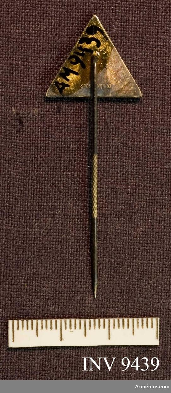 """Märke av typen kamratmärke för Svea livgardes 7:e kompani. Märket har tillverkats av Sporrong AB; det står också antecknat på frånsidan. Märket har triangulär form. Framsidan i blå metall. I mitten finns Gustav VI Adolfs monogram och längs kanterna står texten: """"Kongl. Svea Livgarde 1976 7 kompaniet 1968"""". Märket tillverkades på initiativ från de värnpliktiga  gardessoldaterna kort innan de skulle rycka ut. Detta exemplar överlämnades till mig som stf plutch 1. plut 7. komp. I 1 i samband med en kamratfest organiserad av de värnpliktiga. Att man valt en """"gammalstavning"""" härleder jag från den ökade dimension i identiteten som de värnpliktiga hade fått genom julhögvakterna 1967 i m/ä. Jag kan inte minnas att något av allt detta utgick från befälen, utan de värnpliktiga (vissa) sökte identitet i förbandshistorien och dessa symboler. Kompanichef var dåv kaptenen Ulf Gabrielsson, stf kompch lt Björn Cronlund. Min plutch hette Henry Sjöö och var fanjunkare. Det finns en poäng i detta sammanhang: Underofficerskåren hade hemställt hos sekundchefen att de måste utgöra plutch, från att tidigare (ständigt) tjänstgjort i stf plutch-befattning inom utbildningsbataljonen. Sekundchefen bestämde att 6. komp skulle ha off och plutch medan 7. komp skulle ha uoff som plutch. Detta ledde till en tävlan, t ex vid de olika soldatproven och under batövningar. Jag kan inte minnas att vi befäl särskilt starkt framhävde denna skillnad mellan kompanierna. Möjligen utgjorde denna sista kontingent före 1968 en anmärkningsvärt positiv och lite ifrågasättande grupp värnpliktiga. 68 kom så hela förskjutningen i disciplinsystemet, uniformstvångets upplösning samt de ständiga nattpermissionerna. Utbildningsåret 1968/69 var bra mycket tuffare för ett lägre truppbefäl!"""