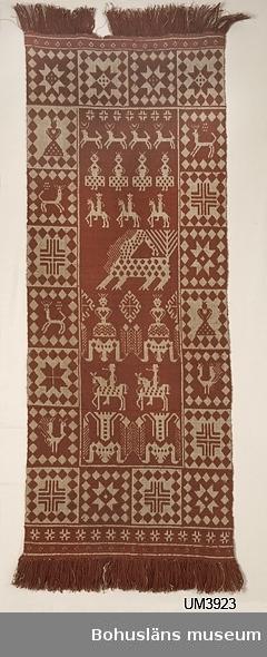 """Rektangulär bonad av oblekt lingarn och hemspunnen ull, växtfärgad med krapp. Mönstret består av en ca 15 cm bred bård med mönstermotiv i rutor (stjärnor, kors, hjortar fåglar, kvinnor) och en mittspegel med mönstermotiv i rader. Namnen på mittspegelns figurer nämns i på baksidan fastsydd lapp med texten: Kopia Ägare: U-a museum Inköpt 1934 Föremålets art: Bonad Figurerna:  1:sta raden: """"Hjortar""""  2:dra """"Fåvitska jungfrurna""""  3:dje """"Ryttarna å svarta hästen""""  4:de """"Draken""""  5:te """"Visa jungfrurna""""  6:te """"Ryttarna m. tveeggade svärdet"""" Sist: """"Brinnande ljus""""  Teknik o storlek: Finnvävnad 57 x 163 cm (1,50 X 1,55 är överstruket) Material: Ull hemspunnen och växtfärgad o lin Tillverkare: Hedda Mattsson Ödsmål, Solberga, Inlands n:e härad Bohuslän. På baksidan finns även: Fastnäst pappersbit lackstämplad med texten UDDEVALLA MUSEUM. Fastklämd etikett av papper/metall med siffrorna 49967, 186.-. Påsydd linnelapp med siffran 15 påskrivet. Lös etikett från Allmänna svenska distriktslantbruksmötet i Axvall 1935, se bilagepärmen. Enligt den etiketten är """"teknikens ortsbenämning"""" """"Prinsessan och draken/Rättare de visa o fåvitska jungfrurna och draken"""". Ca 5 cm av fransen upptill bortsliten. Blekt. Smutsig, speciellt upptill.  Litteratur: Arlenborg, Ingrid/Feltzing, Ulla, Finnväv Bohuslänsk tradition modernt konsthantverk. Berg, Kerstin, Selma Johansson - väverska och hembygdsforskare i Södra Bohuslän, Skrifter utgivna av Bohusläns museum och Bohusläns hembygdsförbund Nr 41, Uddevalla 1991, sid.232-242. Machschefes, Annelie, Väva finnväv på lätt sätt, sid.62 f.  Ur handskrivna katalogen 1957-1958: Finskvävnad """"Draken"""" L. c:a 150 Längdmåttet taget utan fransarna. Br. 57. Vitt och rött ullgarn. Relativt välbevarad. Ödsmål, Bohusl."""