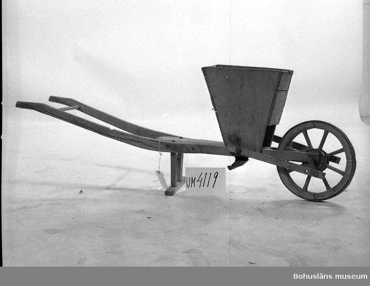 Ur handskrivna katalogen 1957-1958: Bönsåningsmaskin L. c:a 185 cm; lik en skottkärra av trä, m. en trattformig behållare i vars botten sitter ett roterande trästycke, som släpper fram bönorna en och en; trästycket drives av hävarm från hjulet. Hel.  Lappkatalog: 51