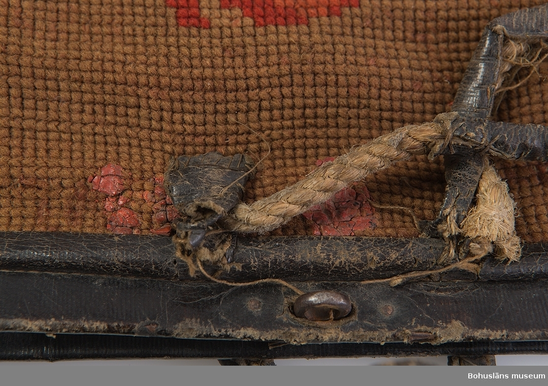 Ur handskrivna katalogen 1957-1958: Kappsäck L. c:a 60 cm. Br. c:a 48 cm. Broderad i korsstygn på stramalj i gulgrönt, rött, blått m.m; ena sid. kvadrater m. blommotiv; andra sid. mansfigur i trädgårdslandskap. Säcken försedd med järnbyglar m. knäppen samt läderhandtag; längs kanterna skodd m. läder. Fodrad; inuti två fack samt en ficka. Föremålet slitet.  Yngwe Segerdahl hade skrotaffär i Uddevalla.