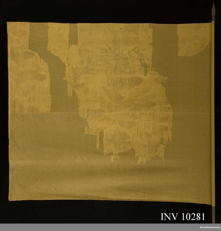 Grupp B I.  Fanduk av vitt siden med diagonalställt, vågigt, kors av gult siden. Målade emblem: krans av två korslagda lagerkvistar med bär, upptill hopknutna med band. Under kransen en fyrkula med 3 (4) flammor. Kransen målad i svart, grönt och brunt. Inskription målad i brunt: FRISCH DRAUF IST HALP GEWUN(NEN).Stång (3,6 m lång) utan spets av grönbrunmålad furu. Nygjord.Tillstånd: Starkt fragmentarisk, duken uppsydd på voille.