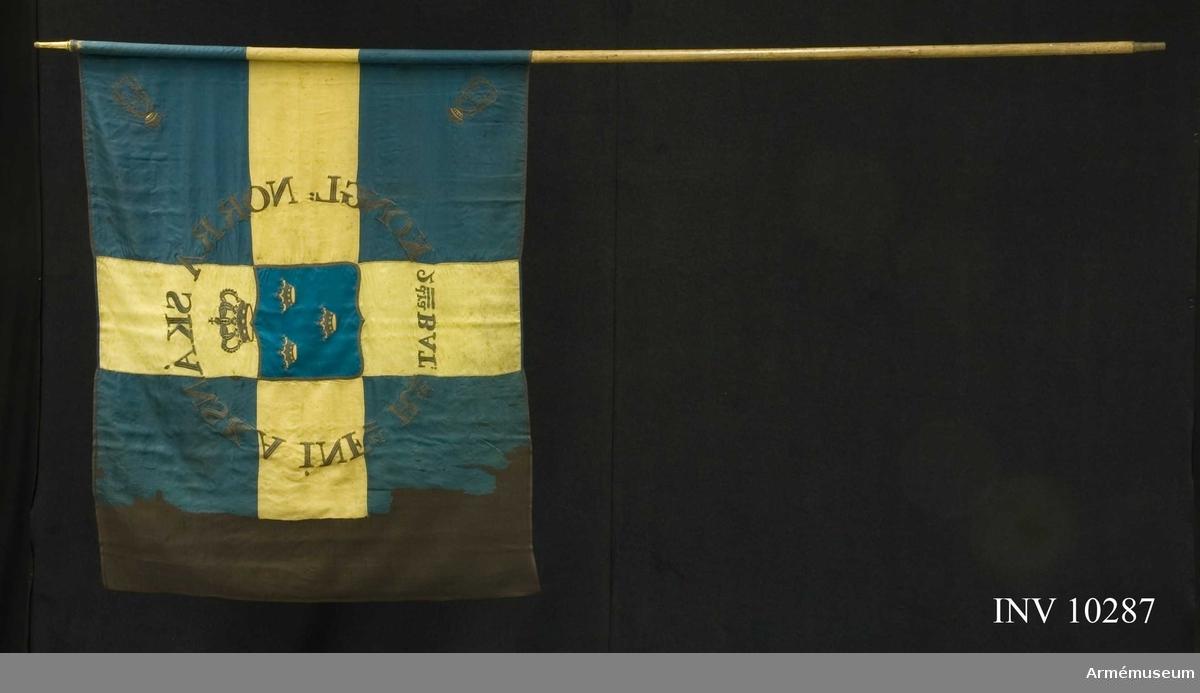 """Grupp B I.  Runt riksvapnet i guld broderat: """"KONGL NORRA SKÅNSKA INFri Rt 2dra BAT"""". Doppsko: 8 cm, holk: 9 cm, spets: 15,3 cm med Carl XIV Johans namnchiffer. Stång av vitmålad furu 292 cm utan spets. Duken konserverad i crepelin, tidigare på nät. De båda yttre namnchiffren saknas. Mörkt blått och gult siden."""