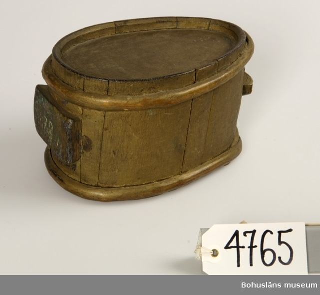 """Ovalt (päronformat) laggkärl. De korta stavarna hålls ihop med hjälp av två parallella träslåar. Det som vanligtvis är botten på laggkärlen är här sidan. Upptill smalnar det av och på toppen är ett hål täljt ur en stav. Nertill står det på en rektangulärt platta som har årtalet """"1784"""" inskuret. Sekundärt målat med bronseringsfärg. Rester av blå färg finns på några ställen under senare påmålat skikt.  Litt.; Nylén, Anna-Maja, Hemslöjd, Håkan Ohlssons förlag, Lund, 1978, s. 371-377.  Ur handskrivna katalogen 1957-1958: Brännvinsdunk, liten """"78"""" Bottenmått: 20,5 x 14. H: 12. Bottnen äggformad. Av trä, förgylld. Föremålet helt.  Lappkatalog: 52"""