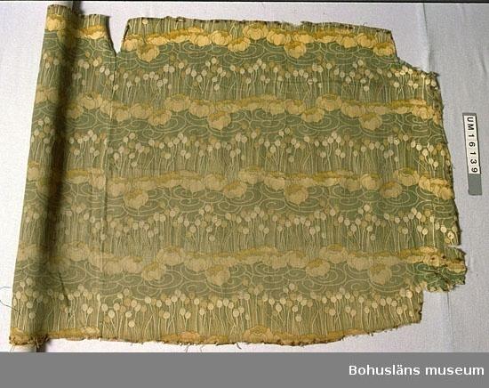 """Halvlinne. Tryckt mönster av näckrosor i rader med mellanliggande rader av kapsal från vallmo, i färgerna grönt, beige, gult och vitt. Slitet och blekt. Har suttit på barnkammarmöbel hos familjen Carl Wilhelmson.  På Carl Wilhelmsons målning """"Konstnärens hustru"""" från 1904 finns ett draperi bakom den avbildade hustrun som ser ut som tyget  som vi har en del av. Ett tyg i tidens anda, ett jugendmönster. Vi vet inte om tyget använts på många platser i det Wilhelmsonska hemmet eller om draperiet syddes om för barnkammarmöbeln."""