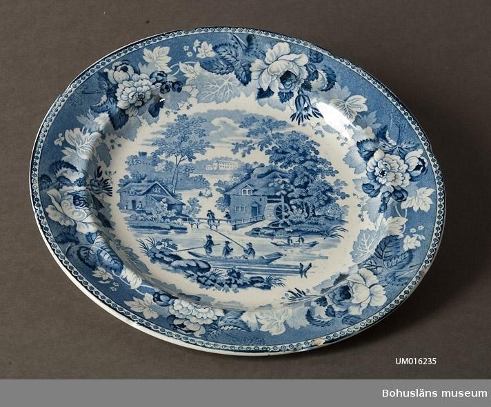 """Ur den s.k """"1828 års servis"""", på vilken man f.f.g använde koppartryckt dekor. Rik täckande dekor med pastoral scen. Anemonbård på brämet. Färg blå."""