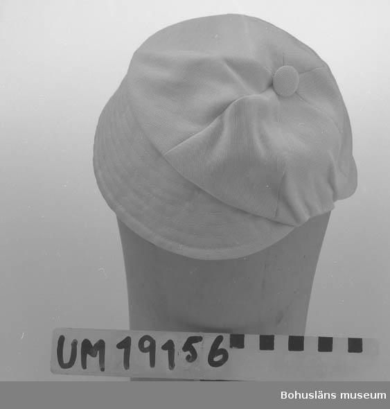 471 Tillverkningstid 1950-TAL 410 Mått/Vikt !  SKÄRMB. 6,5 394 Landskap BOHUSLÄN  Vit hatt med kilar och skärm med stickningar. Klädd knapp upptill.  Se UM19130.