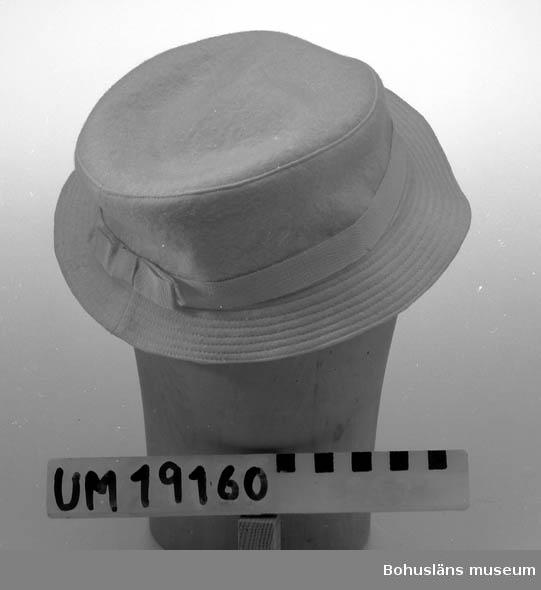 471 Tillverkningstid 1950-TAL 410 Mått/Vikt !H.6,5 BRÄTTB.4 CM 394 Landskap BOHUSLÄN  Vit filthatt med ripsband runt kullen. Stickningar på brättet.  Se UM19130.