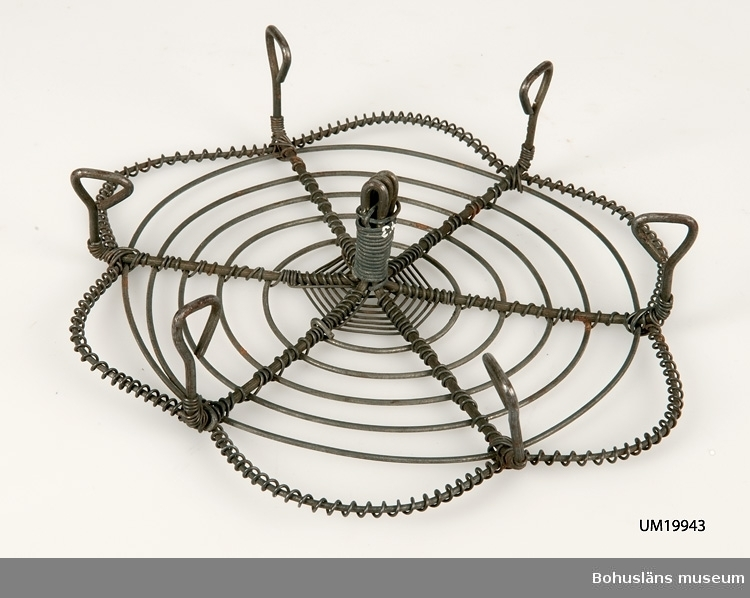 Trådarbete. Sex fötter runt kanten och en i centrum. Översidan av spiral samt uddformad ytterkant.